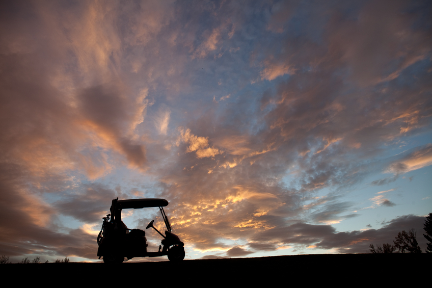 A golf cart silhouette. Power cart is positioned on a golf course on a hill. Set of golf clubs are on the back of the cart. Cart is positioned right behind the sun for drama. Nobody is in the image, which was taken with a Canon Mark II 5D camera body and an L series lens.