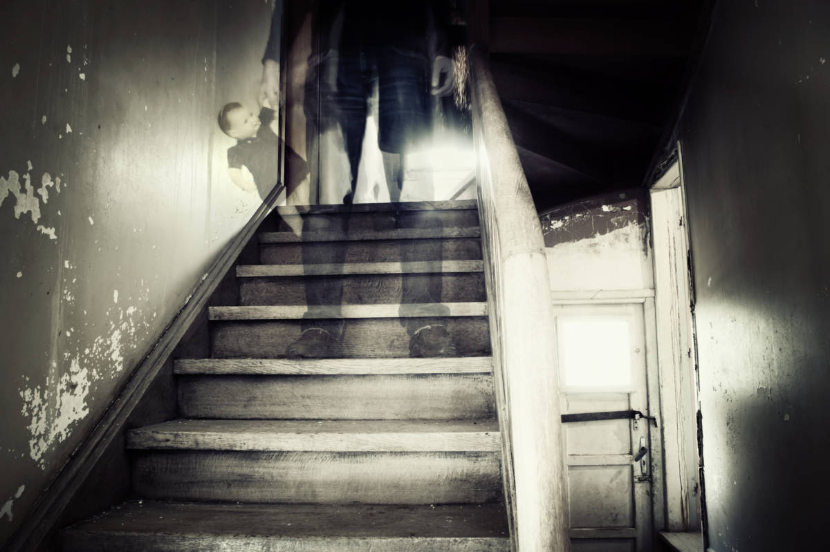 Ghostly figure standing on stairs inside a hounted house holding doll
